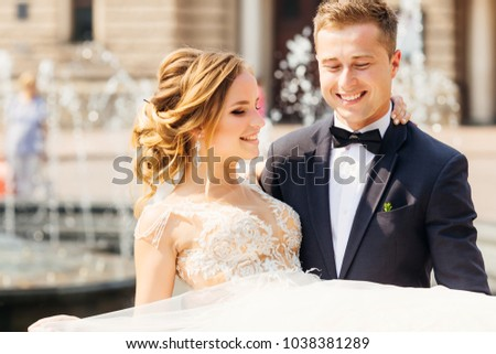 a close-up of a happy groom holding his beloved bride with a beautiful makeup and a chic dress #1038381289