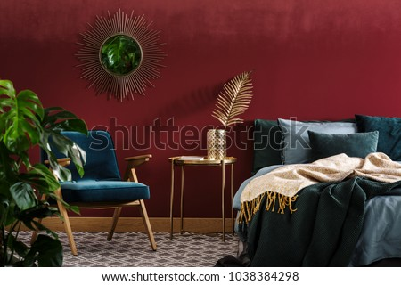Gold table between green armchair and bed in sophisticated red bedroom interior with mirror #1038384298