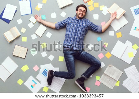 Young man isolated on grey background with papers and notes smiling cheerful #1038393457