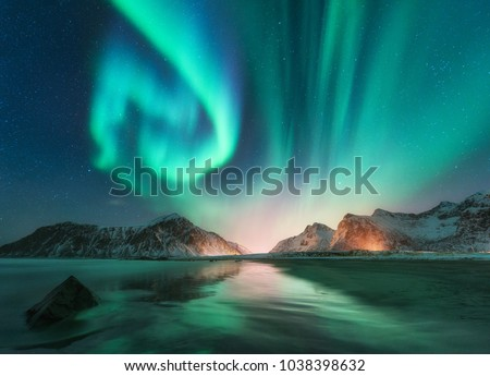 Aurora borealis in Lofoten islands, Norway. Aurora. Green northern lights. Starry sky with polar lights. Night winter landscape with aurora, sea with sky reflection, stones, beach and snowy mountains #1038398632