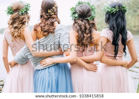 three bridesmaids in powdery dresses transformers and wreaths on the head embrace the bride in a blue dress #1038415858