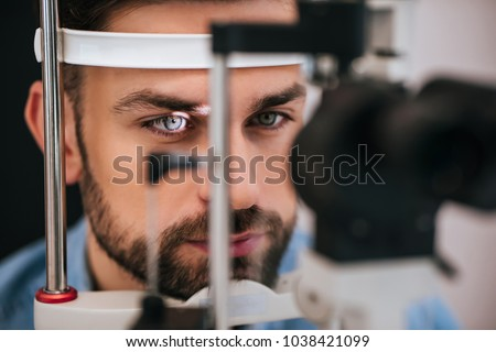 Handsome young man is checking the eye vision in modern ophthalmology clinic. Patient in ophthalmology clinic #1038421099