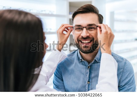 Young female doctor ophthalmologist is helping handsome man to choose the most appropriate eyeglasses. Doctor and patient in modern ophthalmology clinic #1038422065