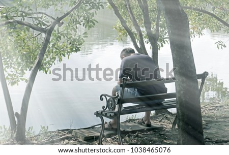lonely man sitting on bench under tree in park with hopeless feeling in front of lake Royalty-Free Stock Photo #1038465076