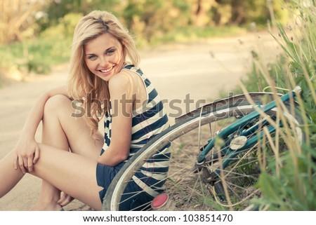 beautiful smiling girl sitting next to bike #103851470