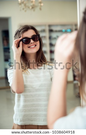 Emotive good-looking caucasian female student escapes from boredom and goes shopping in optician store, standing near mirror, trying on stylish sunglasses, wanting to buy them for sunny spring days #1038604918