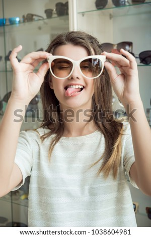 Attractive european female student making faces while on shopping with girlfriend, showing tongue while trying on pair of stylish sunglasses in optical shop, standing over stands with eyewear #1038604981