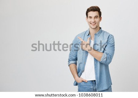 Close-up portrait of healthy handsome caucasian guy with brown hair in denim clothes pointing with one hand and holding another in pocket, being happy and smiling broadly over white background #1038608011