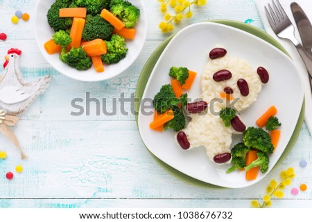 Fun food for kids - cute panda bear shaped rice with kidney beans and vegetables, carrots and broccoli. Overhead view #1038676732