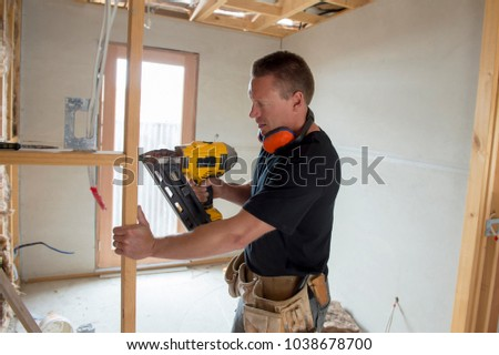 attractive and confident constructor carpenter or builder man working wood with electric drill at industrial construction site in installation and renovation work industry #1038678700