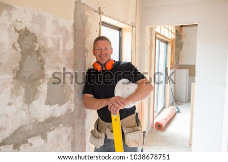 attractive and confident constructor carpenter or builder man with ear protection gear working happy at industrial construction site and installation and renovation work industry #1038678751