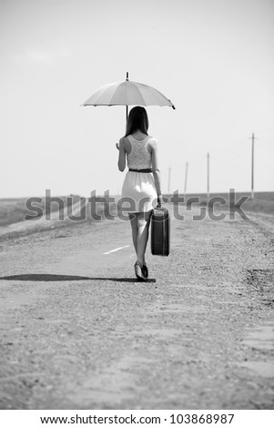 Lonely girl with suitcase and umrella at country road. Photo in black and white style. #103868987