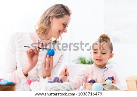 Mother and daughter having fun while painting Easter eggs #1038716479