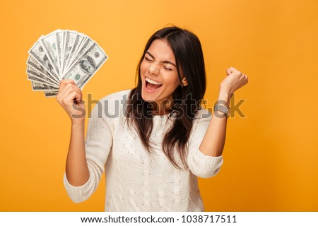 Portrait of a cheerful young woman holding money banknotes and celebrating isolated over yellow background Royalty-Free Stock Photo #1038717511