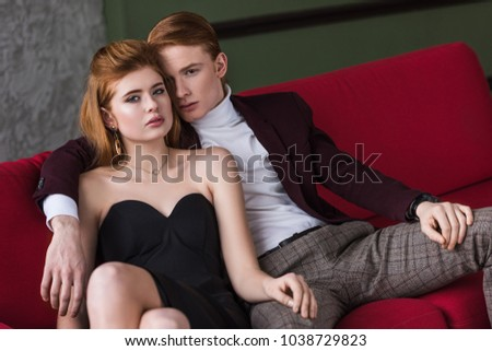 Young female fashion model with earrings and necklace sitting with boyfriend on couch #1038729823