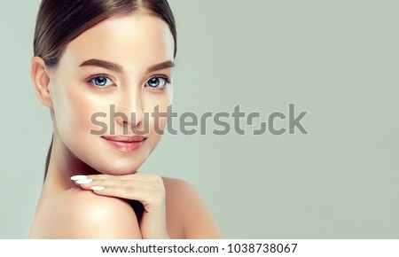Beautiful young woman with clean fresh skin. Girl beauty face care. Facial treatment. Royalty-Free Stock Photo #1038738067