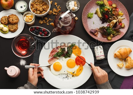 Eating restaurant delicious breakfast with sunny side up fried eggs, bacon, vegetables and greens, croissants and freshly brewed tea served on black table. Nourishing morning meals, top view #1038742939