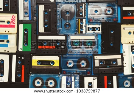 Retro audio cassette tapes on blue background. Top view on vintage media devices, copy space on labels, flat lay #1038759877