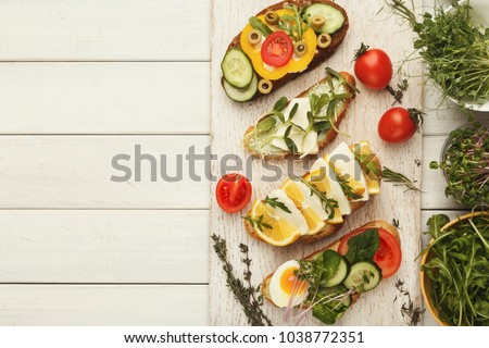 Wholegrain sandwiches and bowls with micro greens. Vegan party food table with organic vegetables bruschettas. Healthy lifestyle and eating right concept, top view on white wood, copy space #1038772351
