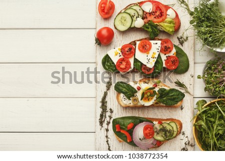 Wholegrain sandwiches and bowls with micro greens. Vegan party food table with organic vegetables bruschettas. Healthy lifestyle and eating right concept, top view on white wood, copy space #1038772354