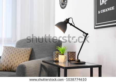 Living room interior with modern lamp on table and comfortable armchair #1038774610
