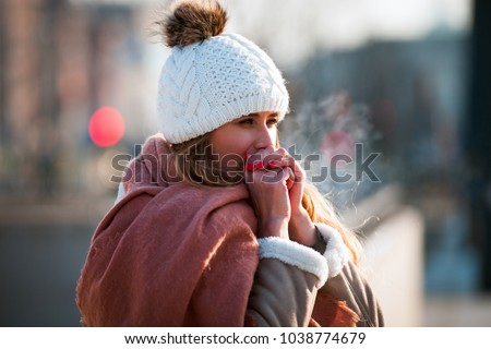 Woman breathing on her hands to keep them warm at cold winter day #1038774679
