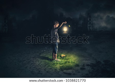 Lost child holding an old lamp in an apocalyptic environment Royalty-Free Stock Photo #1038821770