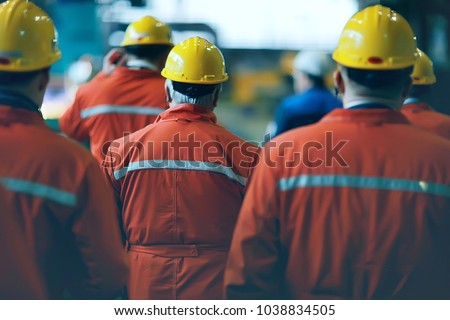 workers  helmets at the factory, view from the back, group of workers,  change of workers in the factory, people go in helmets and uniforms for an industrial enterprise #1038834505