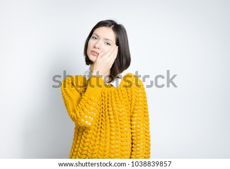 beauty a young woman touching a healthy clean skin, isolated on a gray background #1038839857