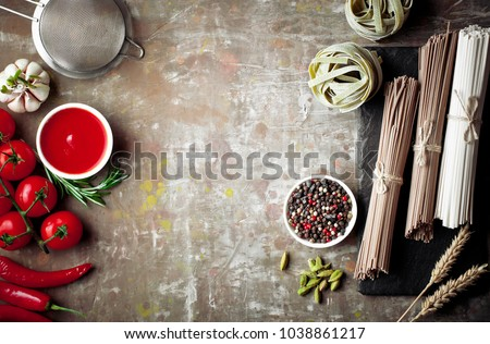 Pasta in a composition with vegetables and kitchen accessories on an old background #1038861217
