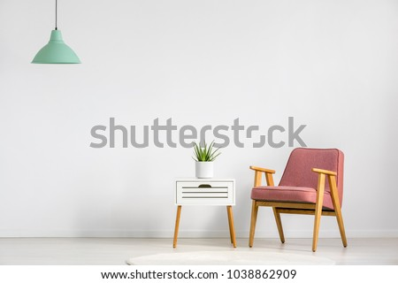 Pink armchair and wooden table on empty wall in simple living room interior #1038862909