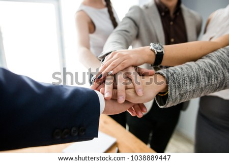 Corporate business team hold hands rejoicing at new victory #1038889447