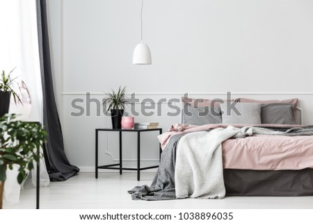 Grey bedsheets on bed in pink bedroom interior with plant on the table against white wall #1038896035