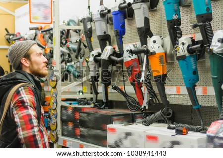A young man chooses angle grinder in the hardware store #1038941443