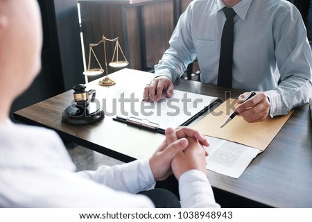 Legal counsel presents to the client a signed contract with gavel and legal law. justice and lawyer concept #1038948943