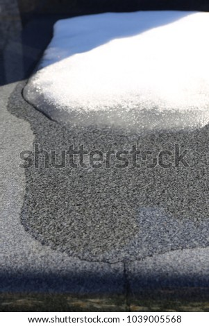 Close up outdoor view of snow and water on a marble plate. Picture taken in a french cemetery in winter just after a snowy day. Abstract urban image, with white, grey and black colors.  #1039005568
