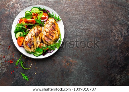 Grilled chicken breast. Fried chicken fillet and fresh vegetable salad of tomatoes, cucumbers and arugula leaves. Chicken meat with salad. Healthy food. Flat lay. Top view. Dark background #1039010737