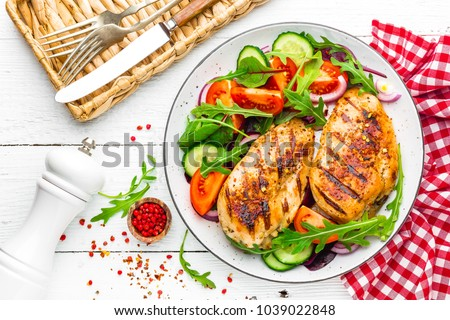 Grilled chicken breast. Fried chicken fillet and fresh vegetable salad of tomatoes, cucumbers and arugula leaves. Chicken meat salad. Healthy food. Flat lay. Top view. White background #1039022848