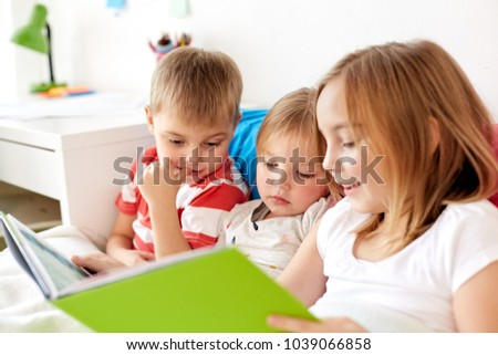 childhood, leisure and family concept - little kids reading book in bed at home #1039066858