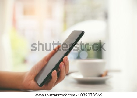 Female hand with smartphone trading stock online in coffee shop , Business concept #1039073566