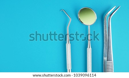 Professional Dentist tools in dental office: dentist mirror, forceps curved, explorer curved, dental explorer angular and explorer curved with chip, right. Dental Hygiene and Health conceptual image #1039096114