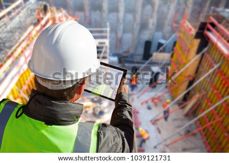 civil engineer or architect with hardhat on construction site checking schedule on tablet computer #1039121731
