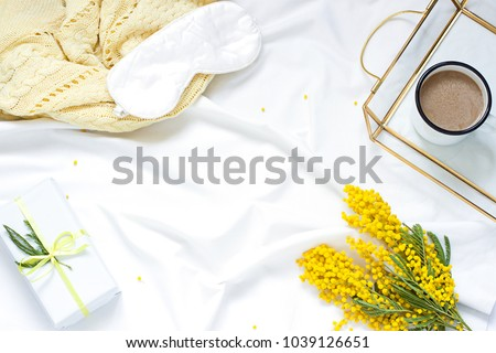 Breakfast in bed white flat lay frame composition with mimosa flowers, a cup of coffee and a gift. Concept woman's or mother's day top view. Copy space  #1039126651