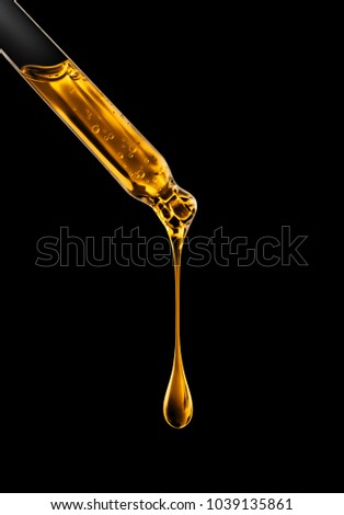 Cosmetic pipette with oily drop closeup on black background #1039135861