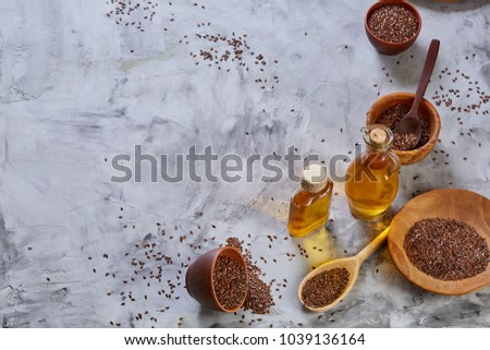 Flax seeds in bowl and flaxseed oil in glass bottle on light textured background, top view, close-up, selective focus #1039136164