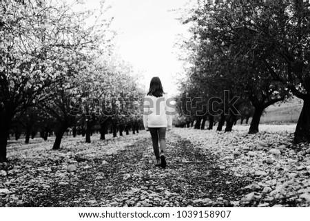 teen girl walking on rural blossom park #1039158907