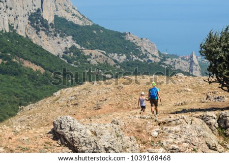 Girl and baby holding hands walking on top of a mountain, view from the back #1039168468