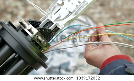 Technicians are installing optic fiber with cable ties. Royalty-Free Stock Photo #1039172032