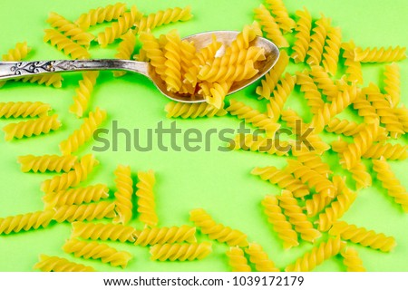 Pasta on Silver Spoon on Green Background. #1039172179