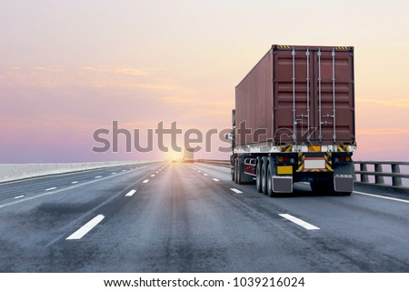 Truck on highway road with red  container, transportation concept.,import,export logistic industrial Transporting Land transport on the asphalt expressway with sunrise sky #1039216024